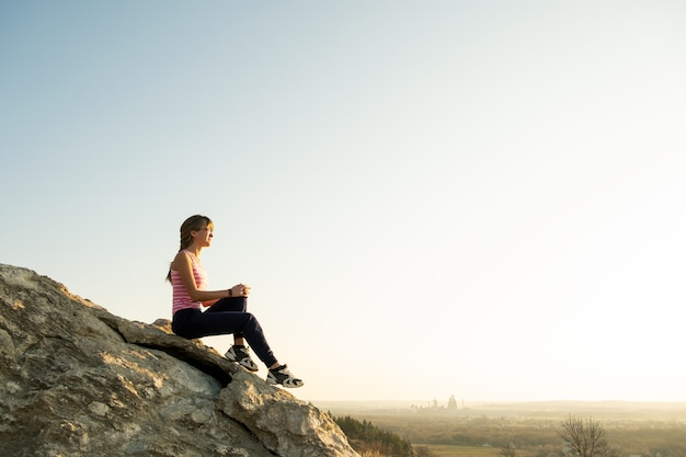 Woman hiker sitting on a steep big rock enjoying warm summer day. young female climber resting during sports activity in nature.