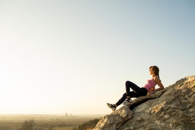 Woman hiker sitting on a steep big rock enjoying warm summer day.