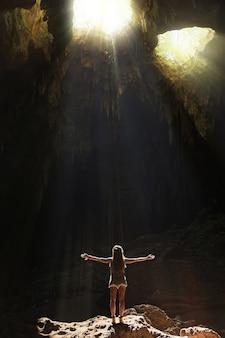 洞窟に立っている女性ハイカー