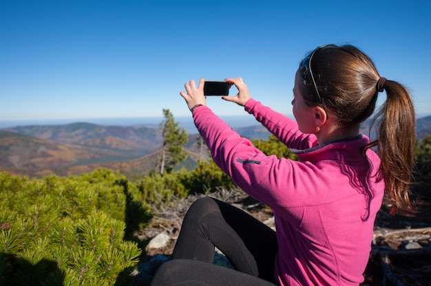 Woman hiker taking photo at the top of the mountain