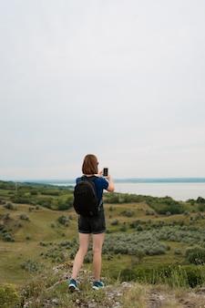 女性ハイカーは丘の頂上でスマートフォンで写真を撮影。