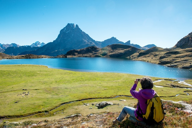 Woman hiker taking picture from the pic ossau, france