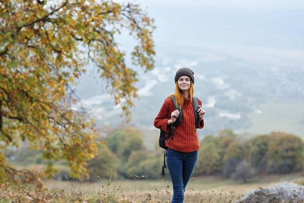 山の秋の木の休暇で女性ハイカー旅行
