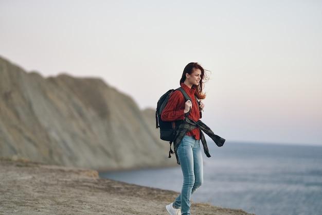 女性ハイカーは彼女の背中の赤いセーターの岩にバックパックを持って自然の中で山を旅します