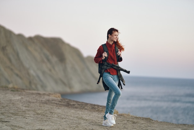 Женщина-путешественница путешествует по горам на природе с рюкзаком на спине красный свитер рок
