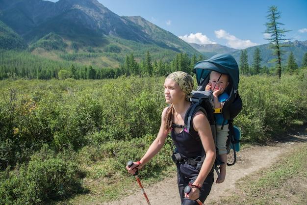 Женщина hiker, треккинг в горах с ребенком в рюкзаке
