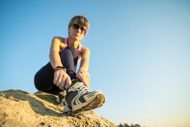 晴れた日に急な大きな岩を登りながら、スポーツブーツの靴ひもを結ぶ女性ハイカー。若い女性の登山家は、困難な登山ルートを克服します。自然の概念のアクティブなレクリエーション。