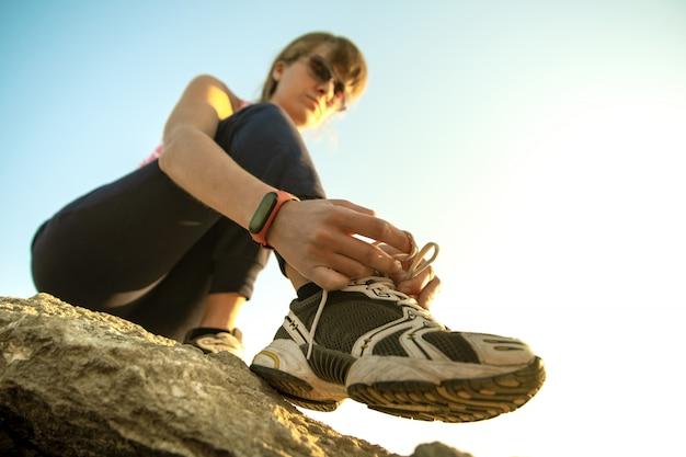 화창한 날에 가파른 큰 바위를 등반하는 동안 그녀의 스포츠 부츠의 신발 끈을 묶는 여성 등산객. 젊은 여성 산악인은 어려운 등반 경로를 극복합니다. 자연 컨셉에 적극적인 레크리에이션.