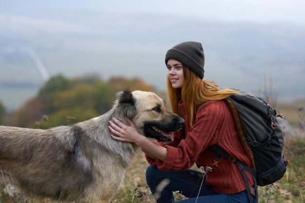 Женщина туристы отпуск путешествия природа весело играя с собакой