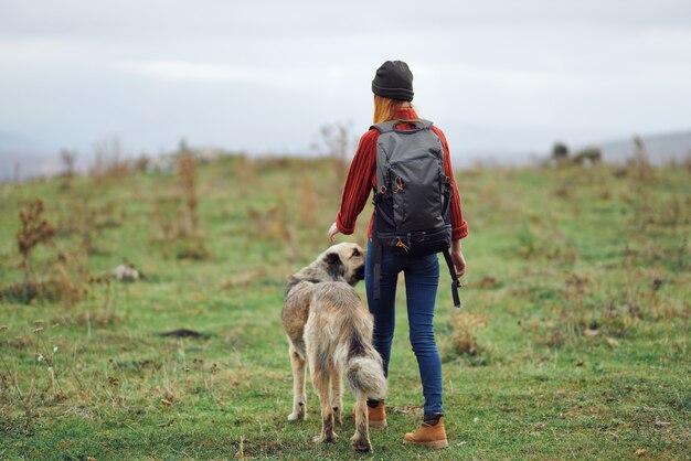 犬の自然の山を歩く女性ハイカー旅行