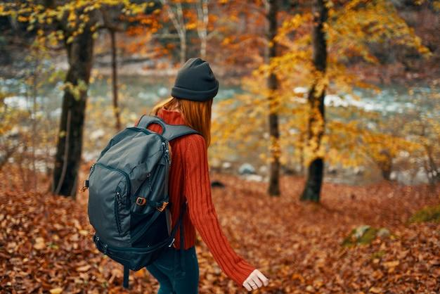 秋の森を歩く女性ハイカーが新鮮な空気を旅する