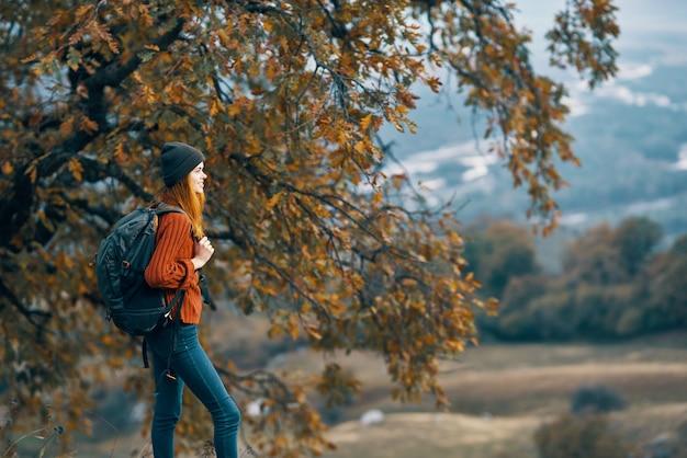 山の木の旅行風景の中を歩く女性ハイカー