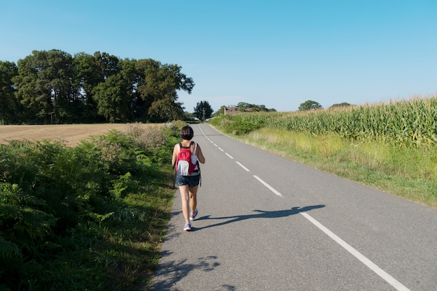 Woman hiker walking on the road