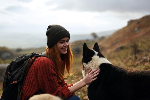 山の自然旅行風景の中の犬を歩く女性ハイカー