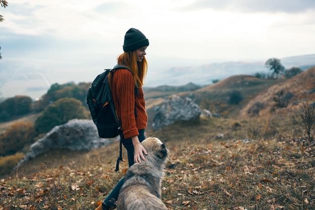 山の自然旅行の風景の中の犬を歩く女性ハイカー