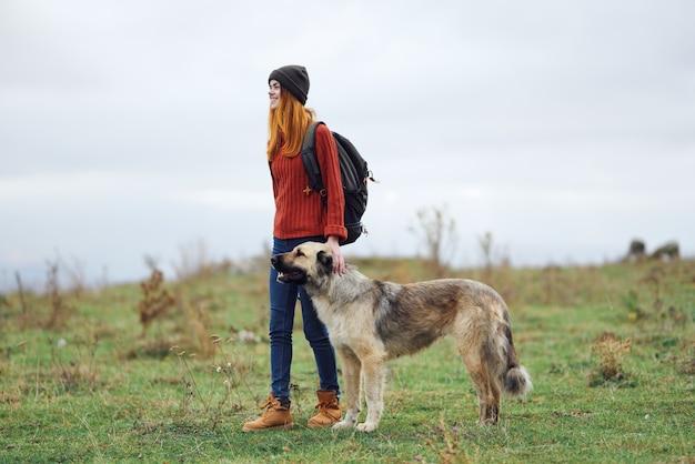 山の旅で犬を散歩する女性ハイカー