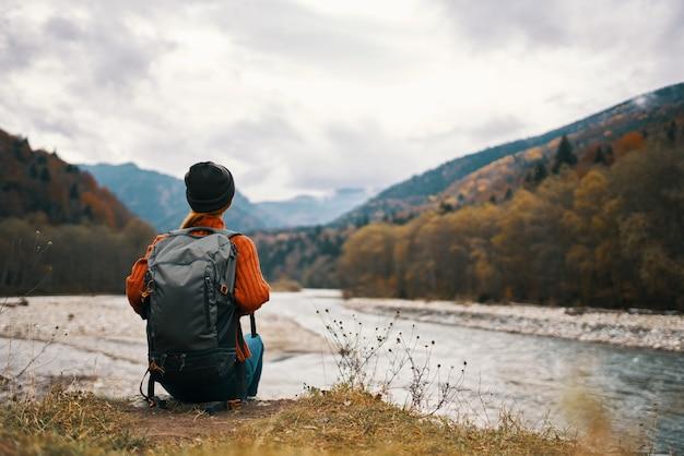 女性ハイカーが川の山の近くを歩く自然旅行