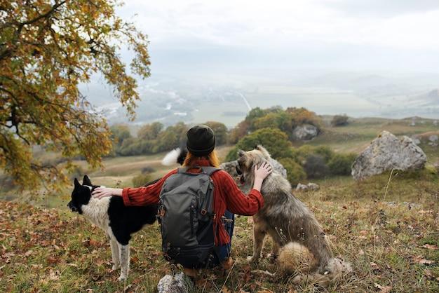 Путешественница женщина с рюкзаком на природе гладит собаку путешествие