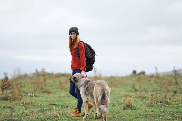 自然の中でバックパックを背負った女性ハイカーは、山の友情旅行で犬を散歩します
