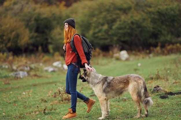 犬と自然の中でバックパックを持つ女性ハイカー。高品質の写真