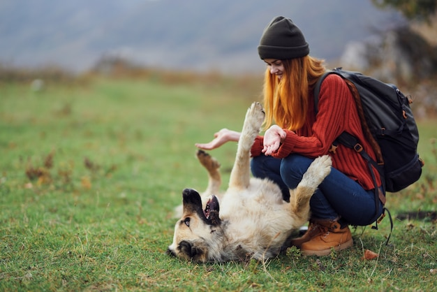 Путешественница с рюкзаком в поле играет с собакой