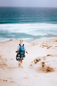 Woman hiker with backpack going down a sand dune towards the lonely beach. sao vicente cape verde.