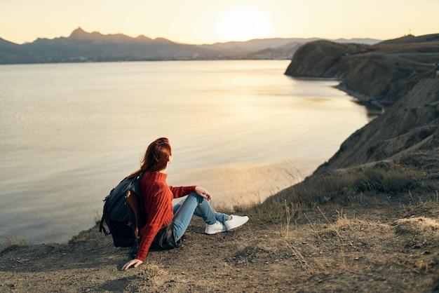 海の近くの日没時に山でバックパックと女性ハイカー