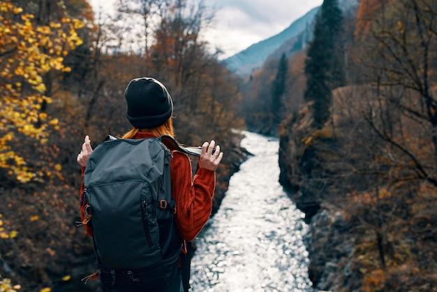 山の秋の森でバックパックを持つ女性ハイカー