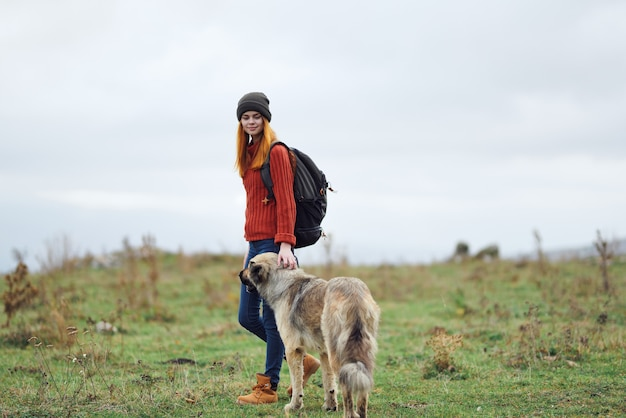 Woman hiker with a backpack in nature walks the dog in the mountains friendship travel