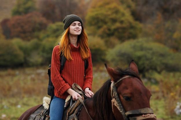 バックパックを持った女性ハイカーは、馬の友情旅行の山に乗ります。