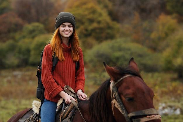 バックパックを持った女性ハイカーが馬の友情旅行の山に乗る