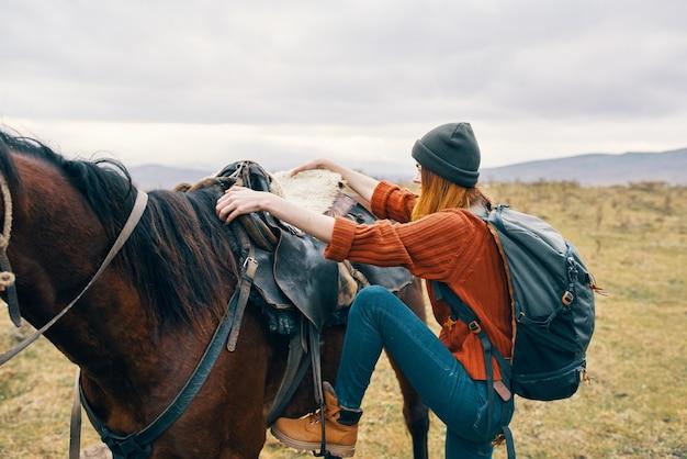 バックパックを背負った女性ハイカーが馬の旅のライフスタイルに乗る