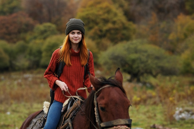 Woman hiker with backpack rides a horse friendship travel mountains. high quality photo