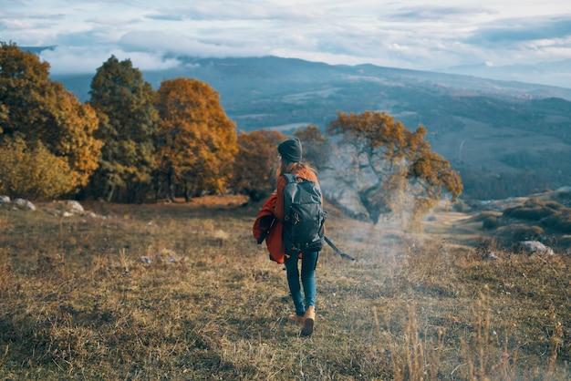 バックパック旅行秋の木々 山々 の風景を持つ女性ハイカー