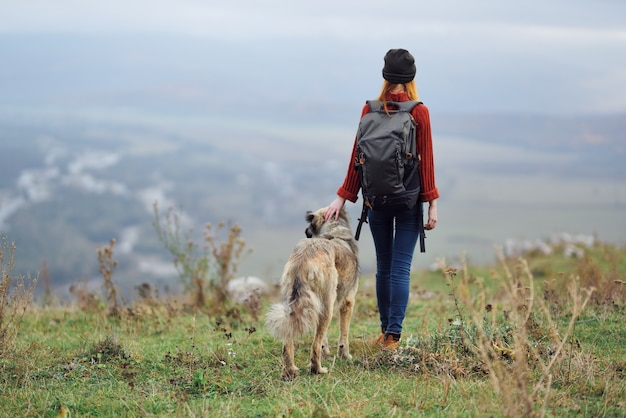Woman hiker with backpack with dog in the mountains travel friendship