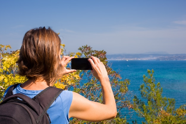 A woman hiker with a backpacker taking a photo of the sea with her smartphone
