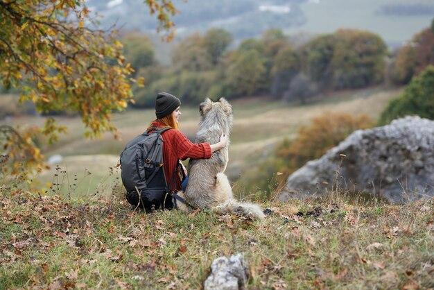 自然の中で犬と女性ハイカー