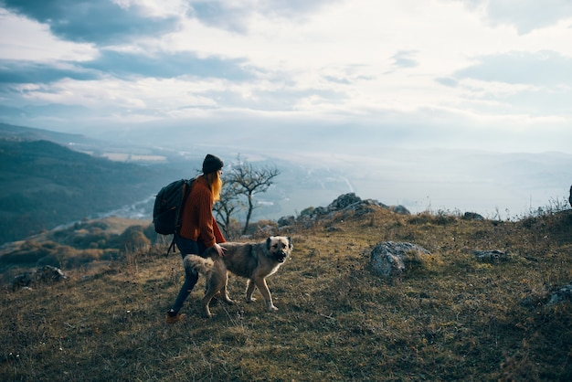 Woman hiker with dog on nature travel mountains landscape fun