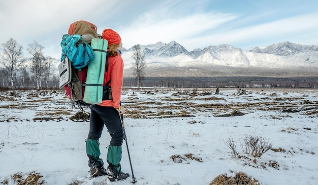 Woman hiker with a large backpack stands with his back looking at the snowy mountains ahead. path to achieving the goal