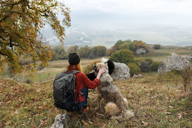 Woman hikers with dogs on nature vacation with backpack