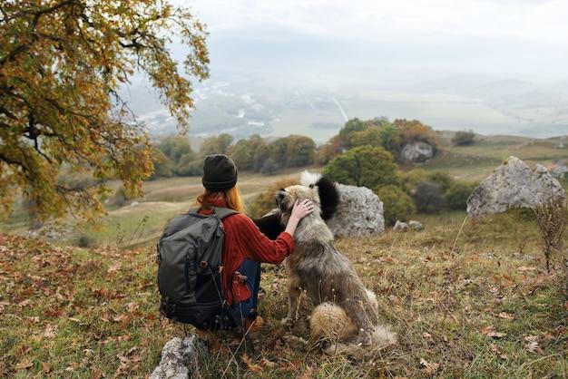 バックパックで自然休暇中の犬と女性ハイカー