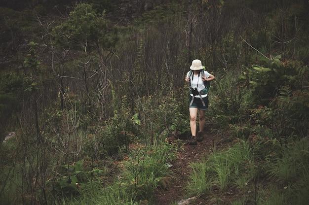 Женщина, путешествующая по горам на закате с тяжелым рюкзаком.