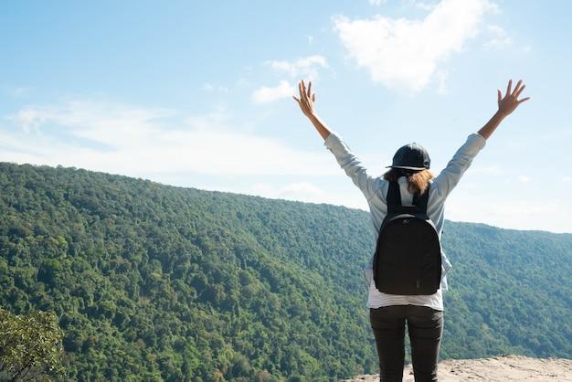 ハイキングをしている女性は、太陽の光のために山の美しい景色をお楽しみください