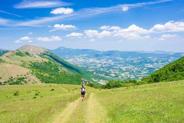 パノラマの景色を望む高原でハイキングする女性