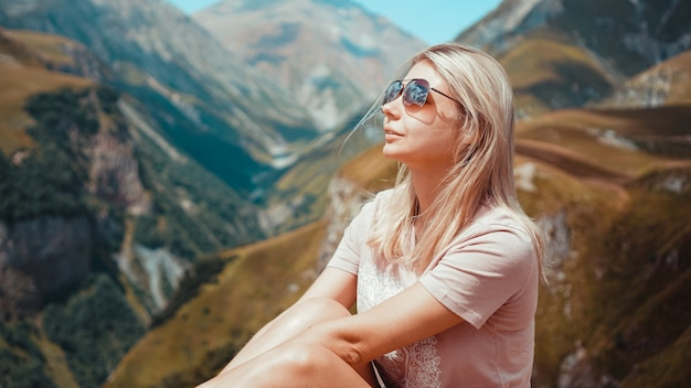 晴れた日の時間に山でハイキングする女性。ジョージア州カズベギの眺め。美しい自然の山の背景