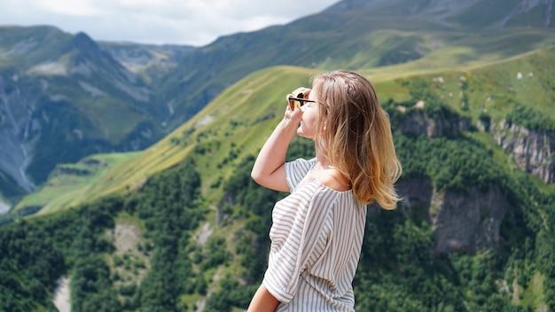 Женщина, походы в горы в солнечное время дня. вид на казбеги, грузия. красивый природный горный фон