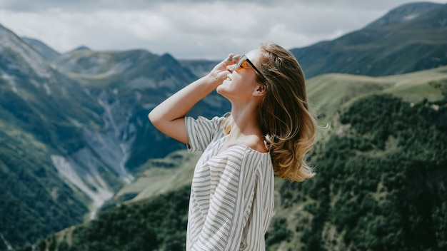 화창한 날에 산에서 하이킹 하는 여자. 조지아주 카즈베기의 전경. 아름다운 자연 산 배경