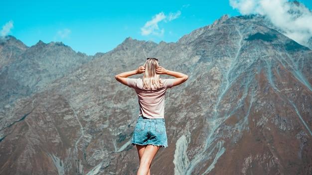晴れた日の山でハイキングする女性