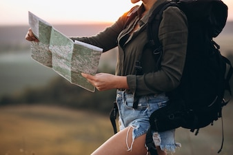 Woman hiking in the mountains and looking in the map