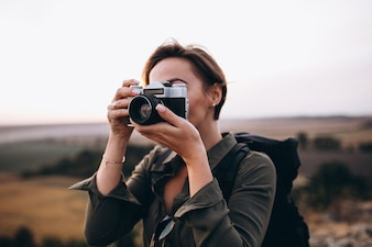 Woman hiking in the mountains and making photo